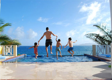 Family jumping into a WIMCO villa pool, St Barths